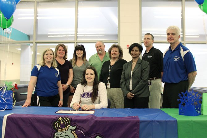Sarah Delaney (sitting), earlier in May, signed her letter of intent to attend James Madison University next school year. There, she will be a part of the Dukes' women's volleyball team. She celebrated her signing moment with family members and school administrators. South Lakes volleyball head coach Cheri Hostetler is at the far left.
