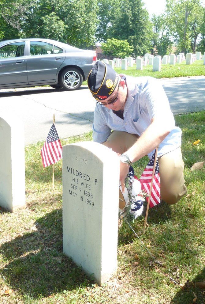 Staff Sergeant Jerome Schorr places a wreath at the grave of former American Legion Post 24 commander F. Clinton Knight during the Memorial Day ceremony at Alexandria National Cemetery.