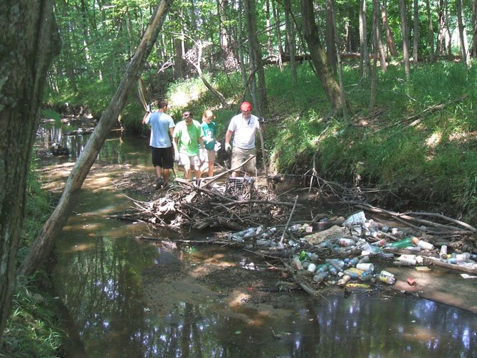 Volunteers remove trash and shopping carts from Little Hunting Creek on May 27.
