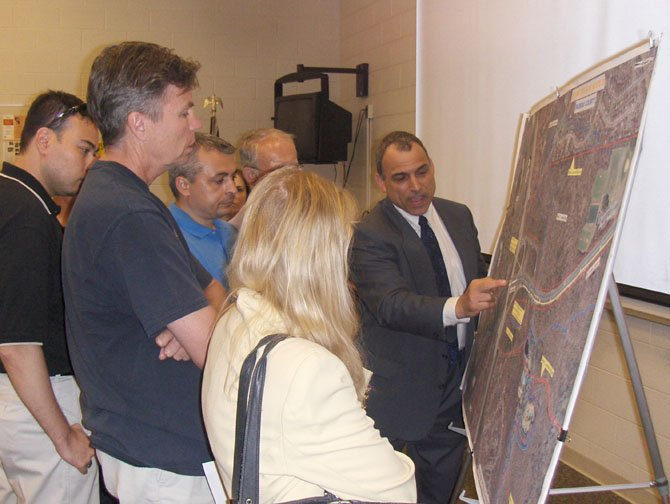 Local residents look at a map showing an aerial view of I-66 and Route 28 in Centreville and Chantilly while VDOT's Bud Siegel answers their questions.