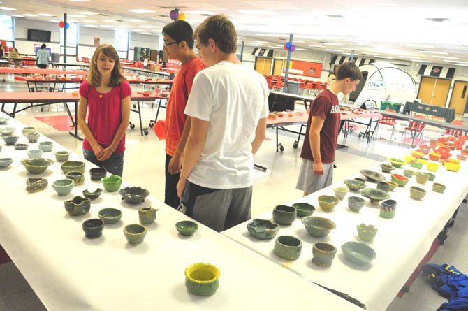 Students at McLean High School examine a selection of bowls made by ceramics students to raise money for Stop Hunger Now, a nonprofit that provides nonperishable meals to the needy around the world.