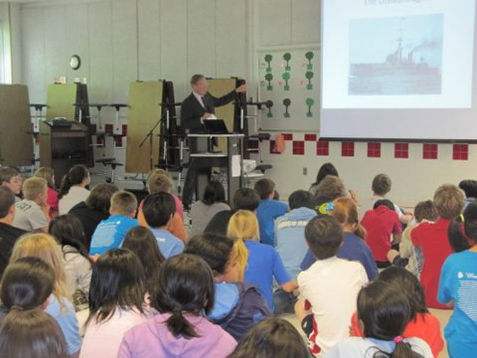 Peter Swiers, retired State Department official, speaks to Churchill Road sixth graders about the school's namesake, Winston S. Churchill.