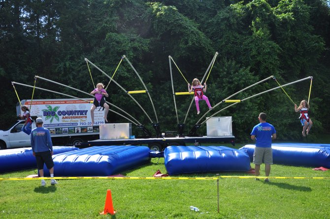 Children jump with the aid of harnesses and bungie cords at the June Fest in Great Falls Sunday, June 3.