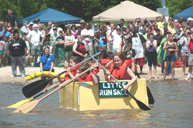 Hundreds of spectators cheer on the participants in the 23rd Cardboard Boat Regatta at Lake Accotink Park on June 3, 2013. This group, from Little Run Elementary School in Fairfax, is working hard to make their way over the finish line before the other competitors in their heat.