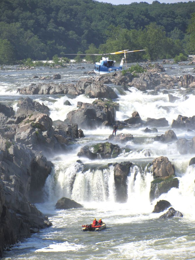 A rescue worker descends from a Park Police helicopter to the rock the kayaker was stranded on as boat units prepare nearby. Nikki Cheshire was awarded First Place in Breaking News Photo at the 2012 Virginia Press Association awards dinner on Saturday, April 20, 2013.