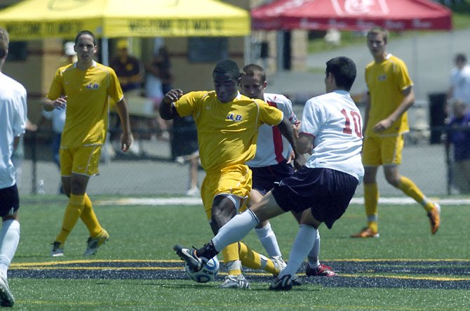 Lake Braddock's Aaron Hollins, with two Albemarle players around him, maneuvers the ball during the Bruins' state semifinals contest at Westfield High School.