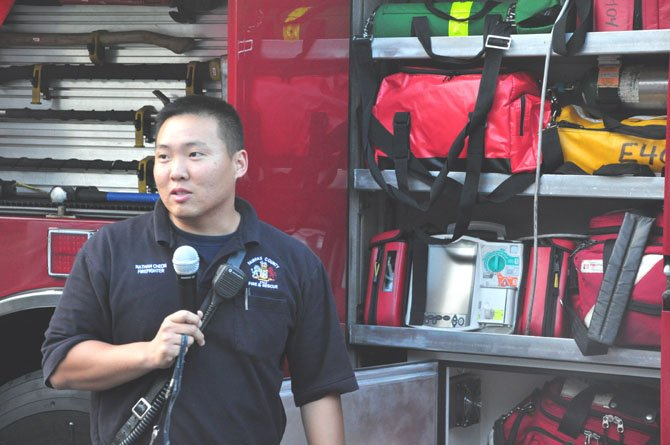 Firefigher Nathan Cheon discusses various features of a fire truck with visitors to the Herndon Neighborhood Resource Center Thursday, June 7.