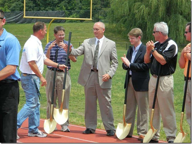 Coach Chris Haddock hands a shovel to outgoing CVHS Principal Mike Campbell, who will be retiring from FCPS this month.