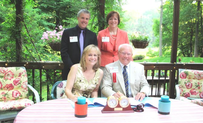 "In the ""Rose Garden"" signing photo, in the front row is Maestra Miriam Burns and President Wayne Winston Sharp, Ph.D. The back row is Executive Director John Huling and President-Elect Aileen Pisciotta, Esq."