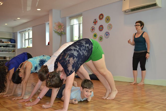 Instructor Linda Feldman leads a group of yoga campers in a downward dog tunnel at Budding Yogis. Specialty camps could be an option for parents still searching for summer activities for their children.