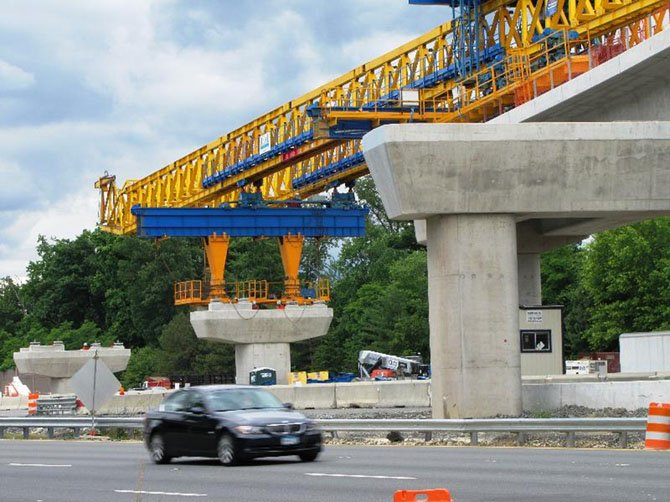 Crews continue to use a huge bright yellow horizontal crane to build the bridges for rail from Route 7 to the median of the Dulles International Airport Access Highway/Dulles Toll Road. This work is expected to be completed in July.