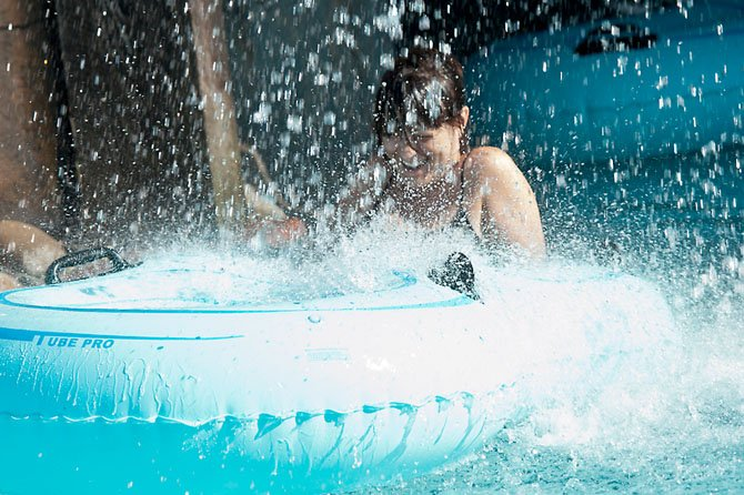 Delcile Philippe of Herndon gets splashed as she rides the lazy river at the Water Mine Family Swimmin Hole at Lake Fairfax in Reston under a waterfall on June 25. 