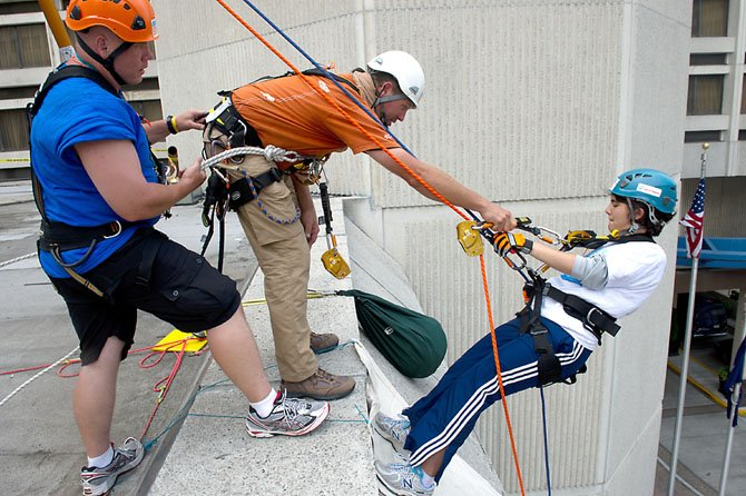 Special Olympics Virginia Athlete Rose Pleskow of Reston gets a helping hand from her ropes master Chris as she starts her 20 foot practice rappel above the entrance to the Crystal City Hilton in Arlington on June 22. After completing the 20 foot rappel, she'll go to the 12th floor, climb up a flight of stairs to the roof, and rappel 100 feet down the outside of the building.
