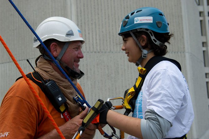 Special Olympics Virginia Athlete Rose Pleskow of Reston gets some words of encouragement from her ropes master before she does her 20-foot practice rappel above the entrance to the Crystal City Hilton.