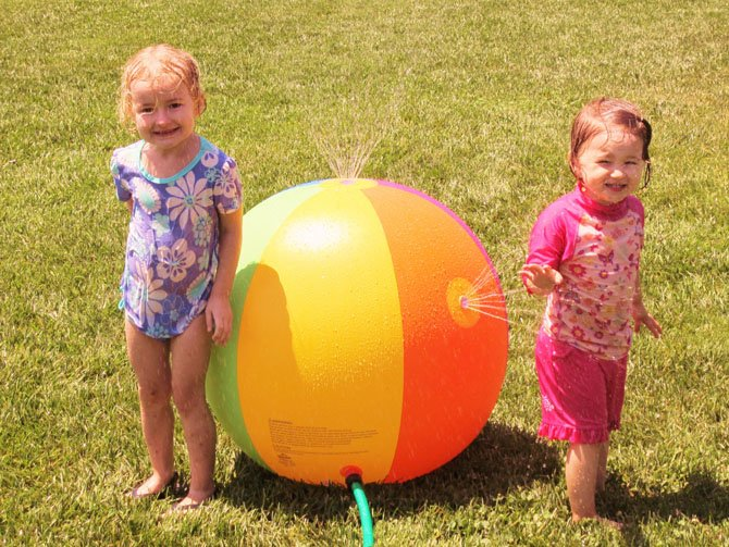 Cassie Geer, 3-1/2, and 2-1/2-year-old Anna Schustereder face off with a water-sprinkling ball.