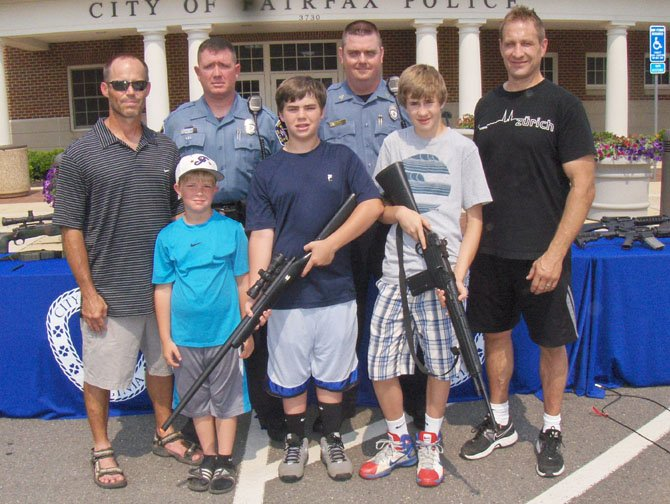 Back row, from left are Bill Wilkinson, SRO Mike Murphy, Sgt. Kyle Penman and Stan Tomajko; with (front row, from left) brothers Eric and Brady Wilkinson and Jordan Tomajko. Brady and Jordan are holding their replica rifles.