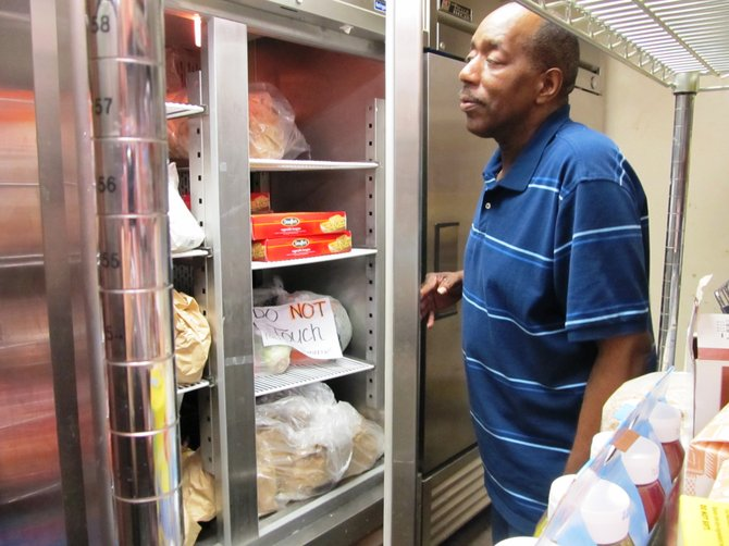 Wilber Shaw, with the Embry Rucker Community Shelter in Reston, checks the pantry's freezer for food on Saturday, July 7.