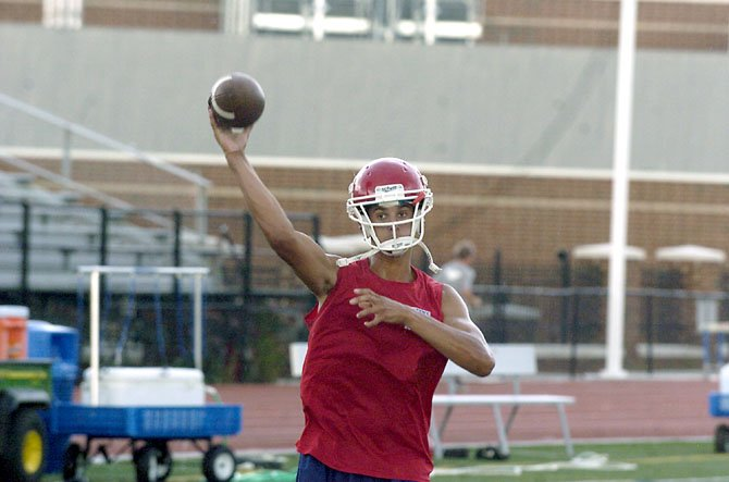 "T.C. Williams quarterback Alec Grosser throws a pass during a ""green"" practice on July 10 at T.C. Williams High School."