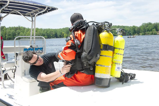 Fairfax County Police Search and Recovery Team divers wear 80 pounds of gear to go in the water. The gear and divers go through multiple safety checks before they dive. PFC Robert Gogan, a member of the dive team and an officer at the West Springfield District adds weights to his colleagues suit to enable the diver to go to the bottom of the Occoquan Reservoir at Fountainhead Regional Park during a training exercise on June 13.