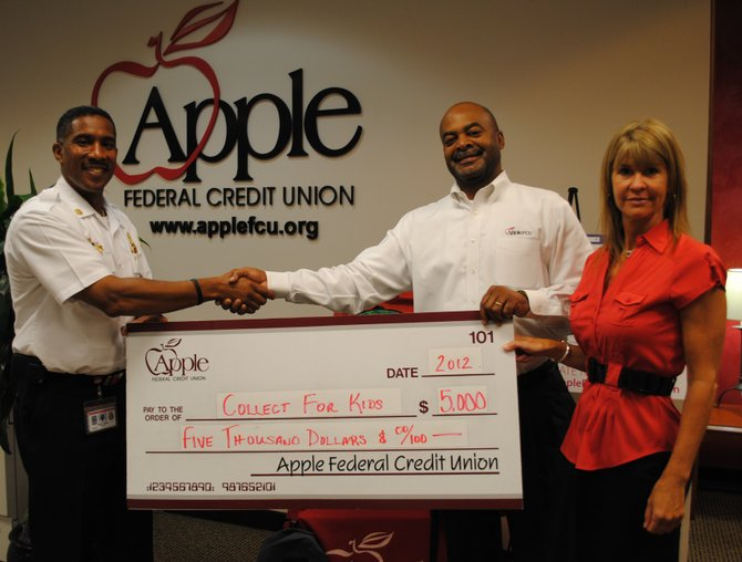 "Apple Federal Credit Union pledges to match up to $5,000 in ""Collect for Kids"" contributions to buy school supplies for low-income Fairfax County children. Shown here left to right are Captain II Willie F. Bailey, aide to the assistant chief of personnel services, Fairfax County Fire and Rescue Department, and from Apple, Robert Sowell, vice president of community relations, and Cynthia McAree, vice president of marketing."