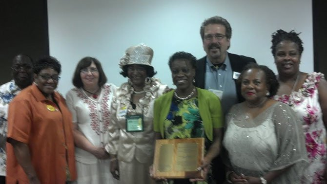 At the Virginia Conference, the Rising Hope delegation receives the Bishop Leontine Kelly Peace and Justice Award. From left are Gerald and Barbara Warren, Kay Barnes, Mary Baker, Yvonne Cunningham (holding plaque), the Rev. Keary Kincannon, Sula Tyler and Jacqueline Martin.