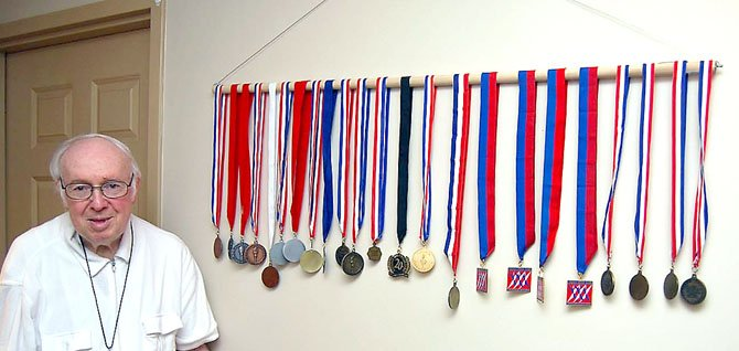 Dr. Ernst with his wall full of medals.