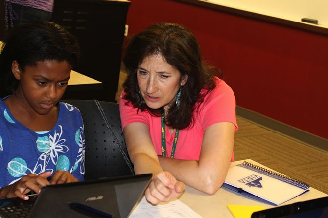 Ann Heidig of Taylor Elementary School in Arlington (right) helps Aliyah Ewell, a rising 6th grader at Mayfield Intermediate School in Manassas City Park, research the composition of space junk.