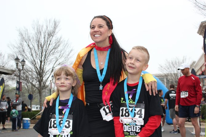 BethAnn Telford of Fair Lakes with her friend Julie's children, Karissa and Landen Stitzel, at the Rev3 Run Rogue 5K in March at Fairfax Corner. Telford will compete in Ironman World Championship in Kona, Hawaii.
