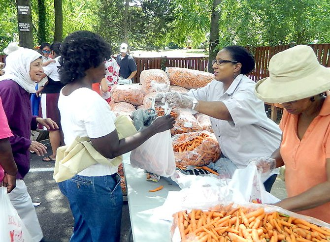 Venisa McCormick serves up the carrots, which arrived at Rising Hope in 50-pound sacks.