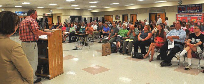Approximately 150 Mount Vernon residents filled the cafeteria at Belle View Elementary School on Monday evening, July 30, for the Westgrove Park Master Plan public information meeting. Linwood Gorham, Mount Vernon representative on the Fairfax County Park Authority addresses the gathering. Standing to the right of Gorham is Sandy Stallman, Fairfax County park planning manager.