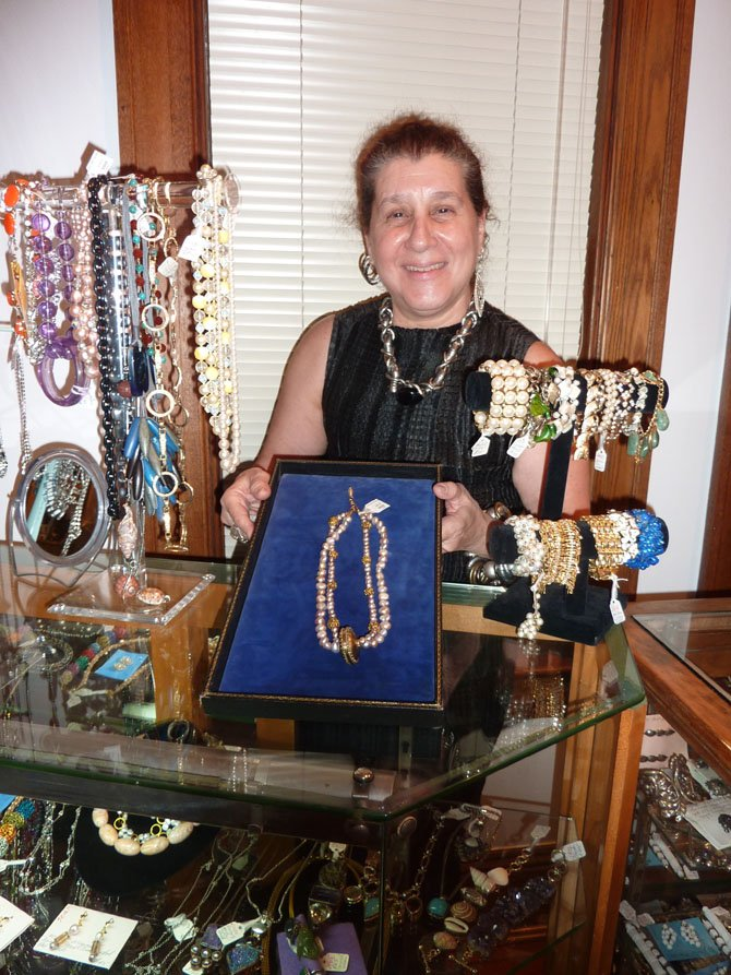 Elinor Coleman displays some of the vintage jewelry available at Vintage Mirage. After eight years on N. Lee St., the Old Town retailer reopened July 3 at 117 S. Columbus St.
