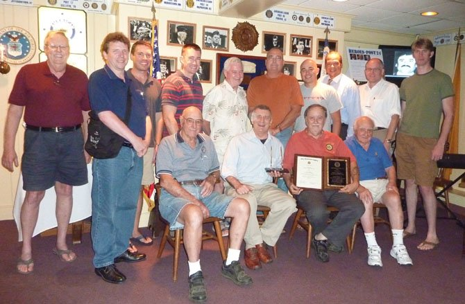 Members of American Legion Post 24 in Alexandria gather to congratulate Jim Glassman, seated second from right, on his selection as Virginia's 2012 Legionnaire of the Year. Pictured standing are (from left) Fred Brink, Erik Campbell, Eric Young, Sam Moore, Jim Taylor, Paul Moffett, Jerome Schorr, Walter Clarke, John Bordner and Eric Beckman. Seated (from left) are Warden Foley, Post 24 Commander Bill Aramony, Legionnaire of the Year Jim Glassman and Bill McNamara.