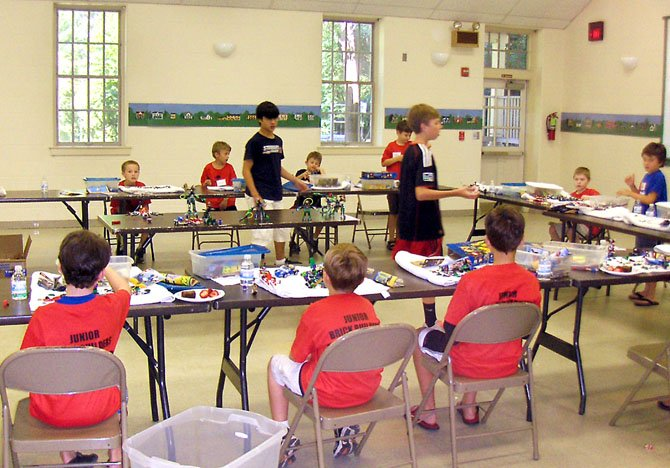 Standing, from left, Evan Cater and Cam Meyer explain LEGO building techniques to the young campers.