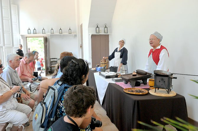 Karen Menatti and Ron Field, historic interpreters at the Mount Vernon Estate, entertain visitors with demonstrations on the making of colonial chocolate and ice cream.
