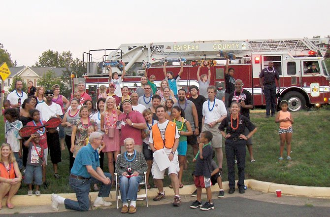 A group shot of residents and Station 38 firefighters at Belcher Farm and Beaumeadow Court. Sheree Glaze and Clint Crawford (in center, in cap and holding flag) organized this block's party with Bill Worthington.