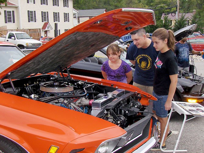Clifton's Mike Nelson and daughters, from left, Lindsey, 9, and Lauren, 13, inspect a 1970 Ford Mach 1 Mustang during the 2011 car show.