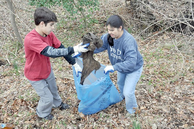 Georgette McKee and her son Maxwell, an eighth grader at Cooper Middle School, pick up trash along Georgetown Pike.