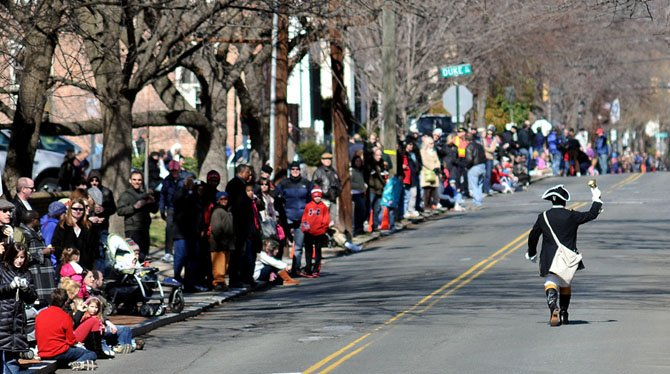 Alexandria Town Crier Ben Fiorre-Walker leads the annual George Washington Birthday parade up S. Fairfax Street.