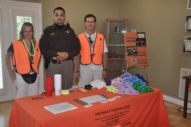 From left are Leslie Jenuleson, PFC Raza Zaidi with the Fairfax County Sheriff's Office, and Dan Jenuleson at Sully Station II's National Night Out event.