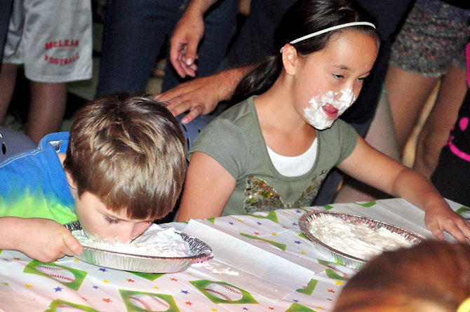 From left, Eli Rutter, 7, and Sofia Belvedere, 10, race against each other in a pie-eating contest at the Old Firehouse Teen Center Saturday, Aug. 25.