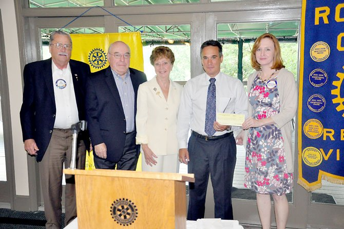 Members of the Reston Rotary Club hand Denise Kellogg (right), of the Colonial Williamsburg Foundation, funding for electronic field trips for six area elementary schools.