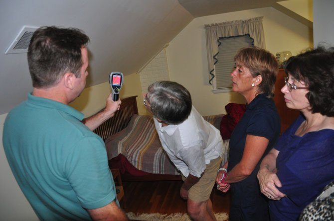 Guests at a McLean residence examine a thermal camera reading from Marty Valentine of Home Performance Solutions Wednesday, Aug. 29. Valentine performed an energy audit as part of a pilot program by Energy Action Fairfax.