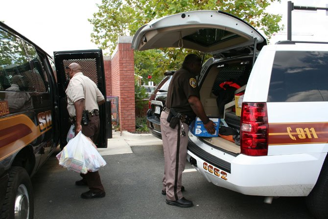 Deputies George Wooden and Mark Jessup pack up school supplies at Charles Houston Recreation Center.