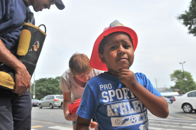 A rising kindergarten student at Douglas Macarthur Elementary School secures his new fire helmet after giving a donation the Firefighter Darrell White.