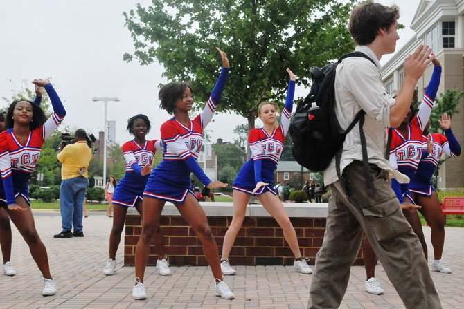 T.C. Williams cheerleaders and members of the school marching band greet arriving students.