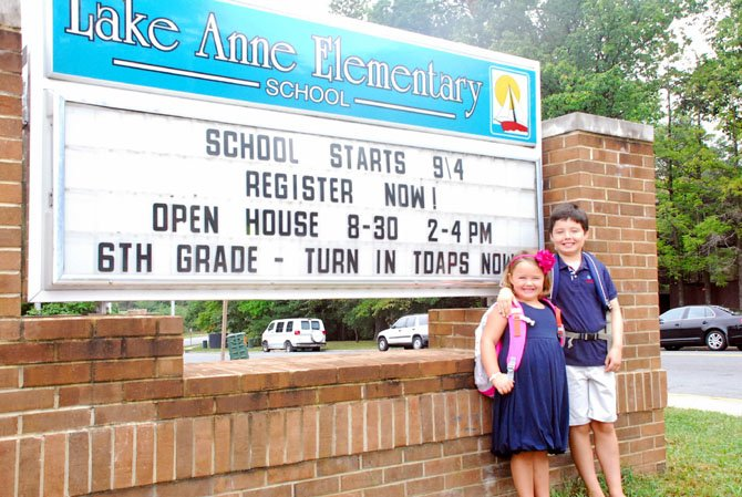 Kindergartener Caroline Kohn poses in front of Lake Anne Elementary with her brother, third grader Will Kohn.