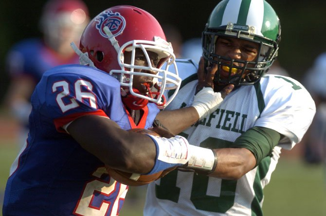 T.C. Williams running back Dealo Robertson stiff-arms Wakefield's Khory Moore during the teams' Aug. 30 contest at T.C. Williams High School.
