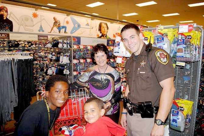 Fairfax County Board of Supervisors Chairman Sharon Bulova and Fairfax County Police Officer Nick Andariese with Justin (left) and Dylan (right) during the 19th annual Shop with a Sheriff event at the Burke Target.