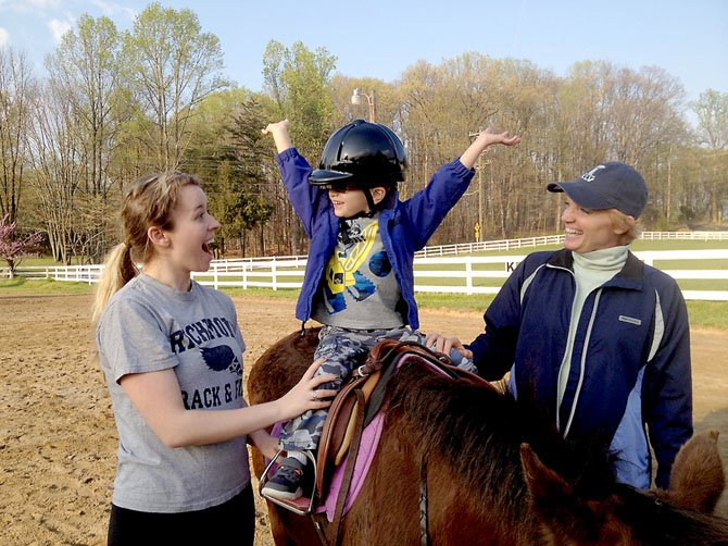 A young rider celebrates a new skill with trainers at the Northern Virginia Therapeutic Riding Program in Clifton.
