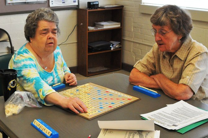 Judy Duncan takes her turn looking for a place to add a new word. Duncan is blind and brings in a Braille Scrabble set. Playing with Duncan are Josie Macdonald and Jean Hayden.